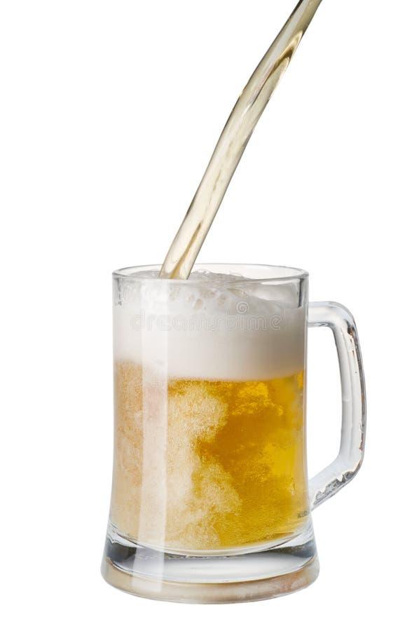 Bière étant plue à torrents dans une tasse d'une bouteille photo libre de droits