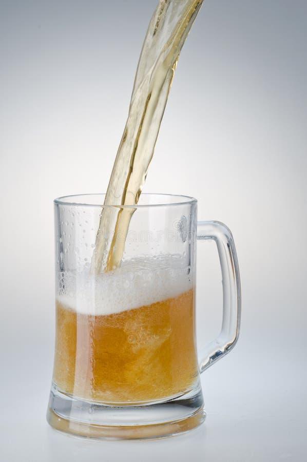 Bière étant plue à torrents dans une tasse d'une bouteille photographie stock libre de droits