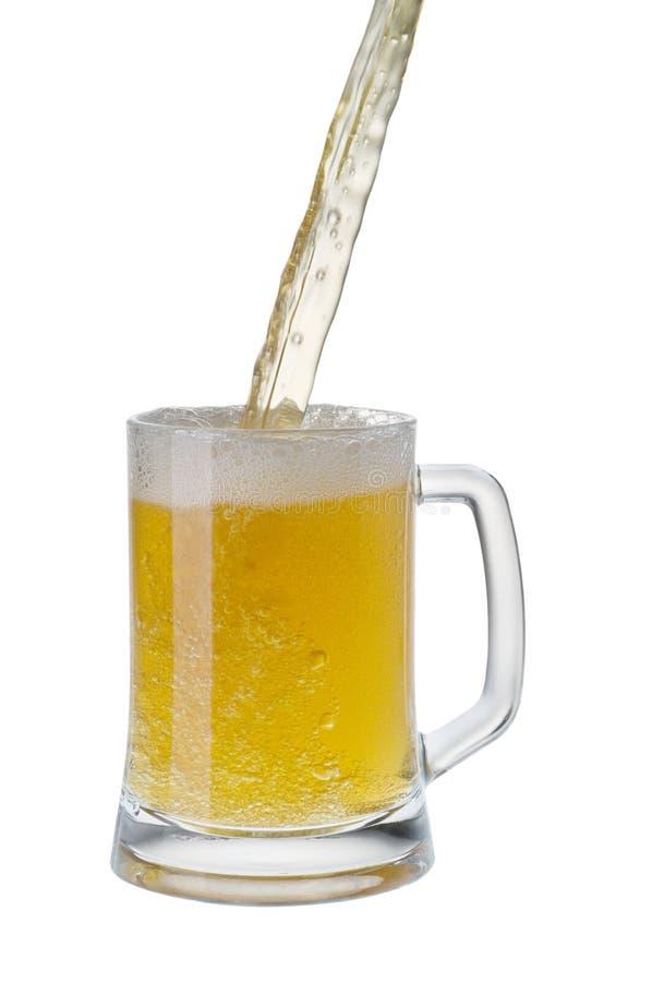 Bière étant versée dans une tasse d'une bouteille image libre de droits