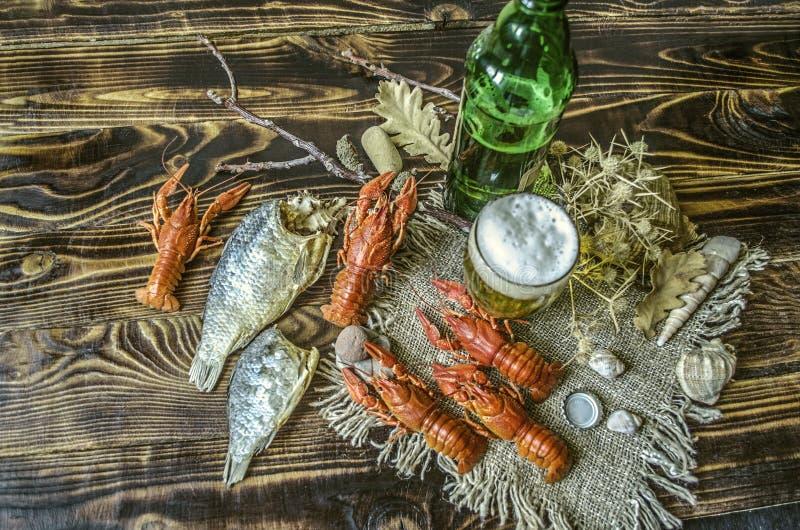 Bière avec la mousse dans un verre et une bouteille de bière avec un casse-croûte des poissons bouillis de jabot et des poissons  photographie stock libre de droits