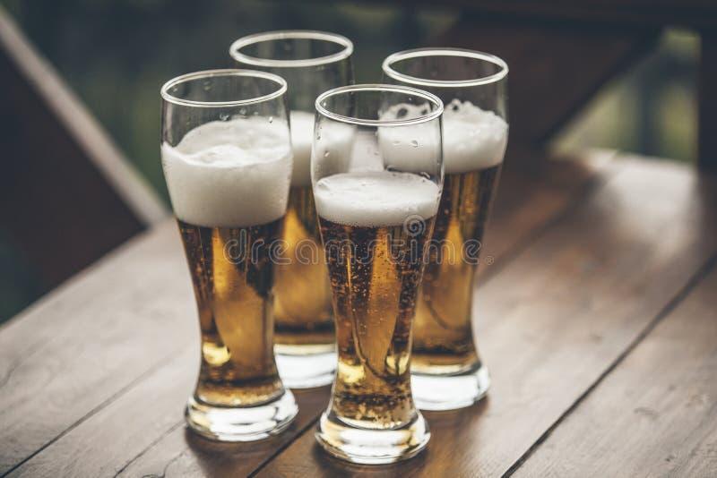 Bière avec les garçons grands de lumière de mousse se tenant sur un closeu en bois de table photographie stock