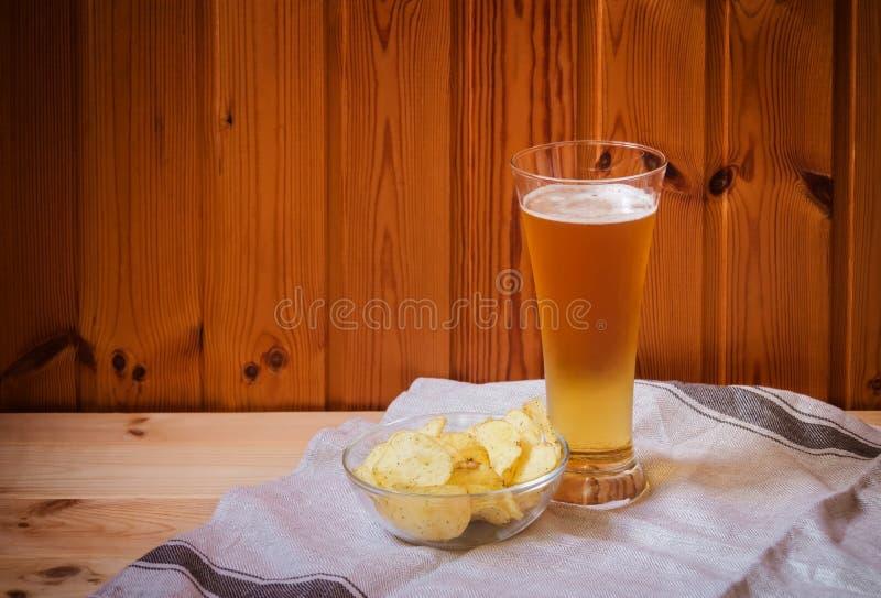 Bière blonde avec des pommes chips dans le bol en verre sur la table en bois photo libre de droits