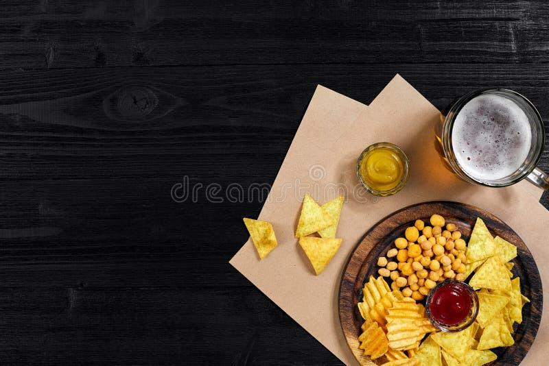 Bière blonde et casse-croûte sur la table en bois noire Écrous, puces Vue supérieure avec Copyspace photographie stock