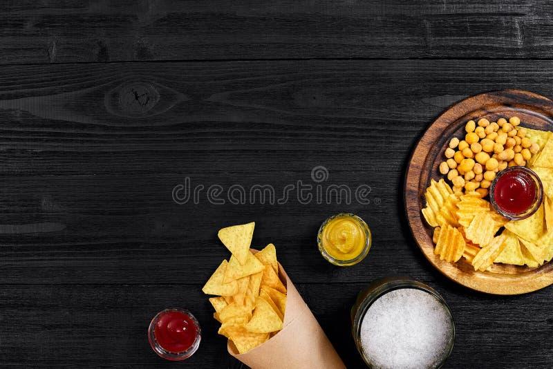 Bière blonde et casse-croûte sur la table en bois noire Écrous, puces Vue supérieure avec Copyspace photographie stock libre de droits