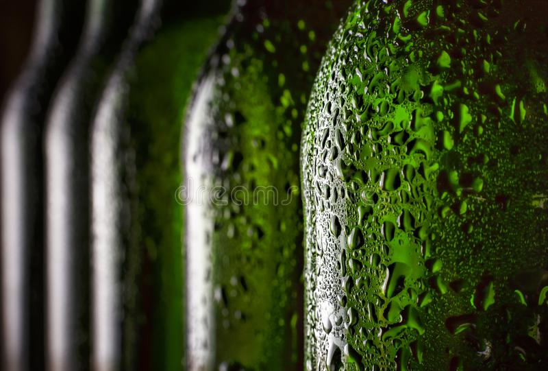 Bière dans la bouteille Plan rapproché Gouttes de l'eau sur une bouteille à bière effrayante Concept : Jour du ` s de St Patrick, photos stock