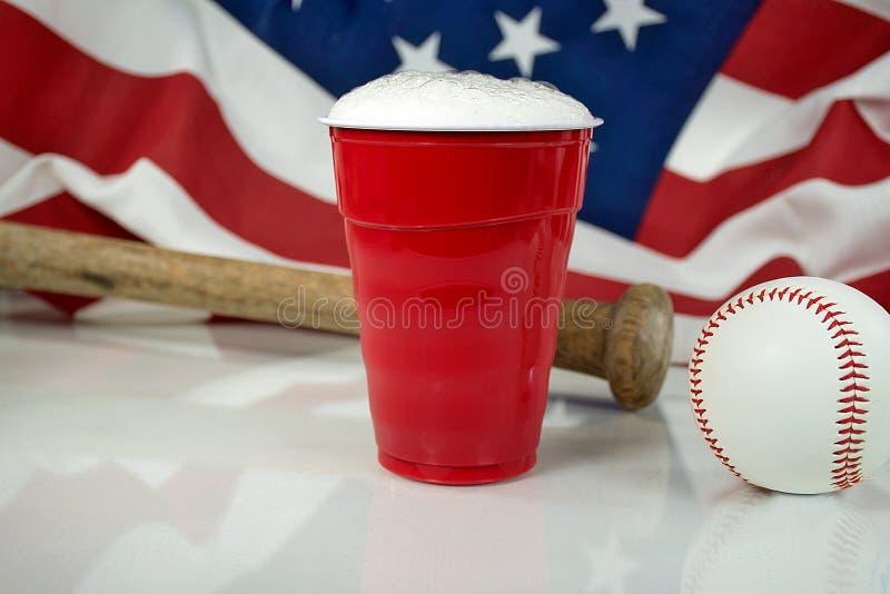 Bière dans la tasse rouge avec le base-ball photographie stock