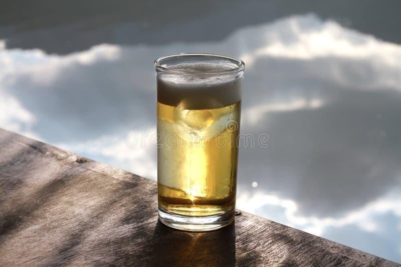 Bière dans un verre d'isolement sur la table en bois photo stock