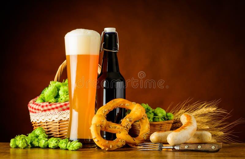 Bière de blé en verre et de bouteille avec Prezel et saucisse image stock