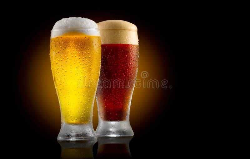 Bière de métier Deux verres de lumière froide et de bière foncée d'isolement sur le noir photographie stock