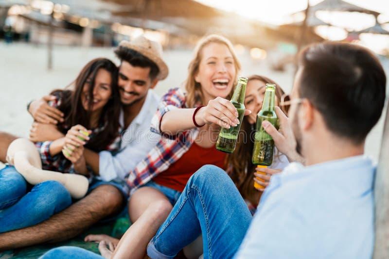 Bière de sourire et potable de couples heureux à la plage photos stock