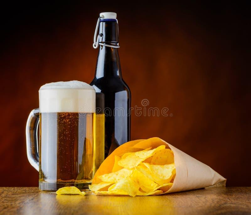 Bière de tasse et pommes chips photographie stock libre de droits