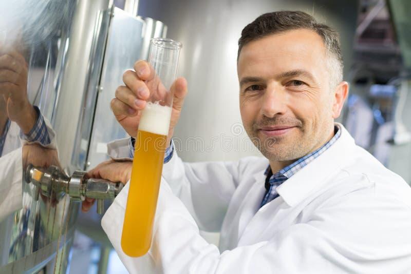 Bière de versement de brasseur dans le cylindre d'hydromètre à l'usine de brasserie images stock