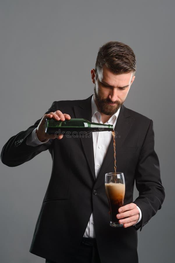 Bière de versement de connaisseur dans le verre photo stock