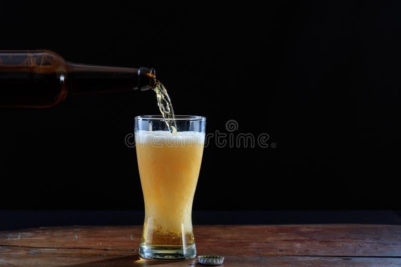 Bière de versement dans un verre sur une table en bois, fond foncé illustration libre de droits
