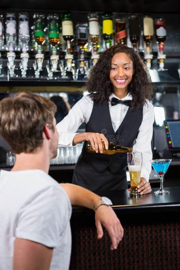 Bière de versement de belle barmaid en verre photographie stock libre de droits