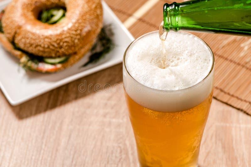 Bière en verre et hamburger sur la table en bois photos libres de droits