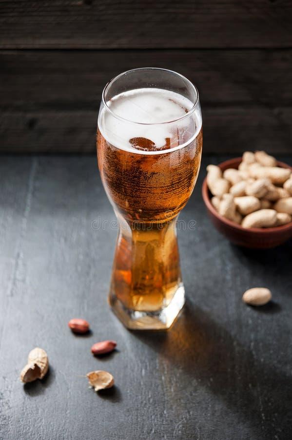 Bière et arachides sur le fond en bois photos stock