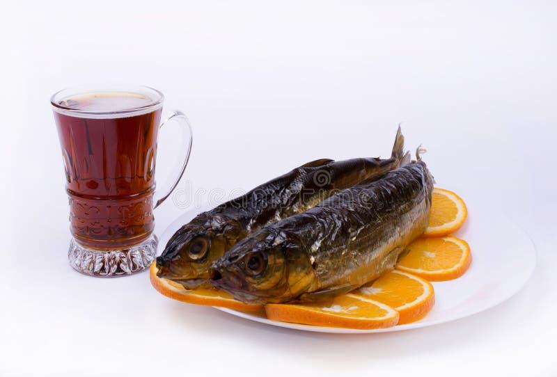 Bière et poissons sur les tranches oranges présentées d'un plat blanc photos libres de droits