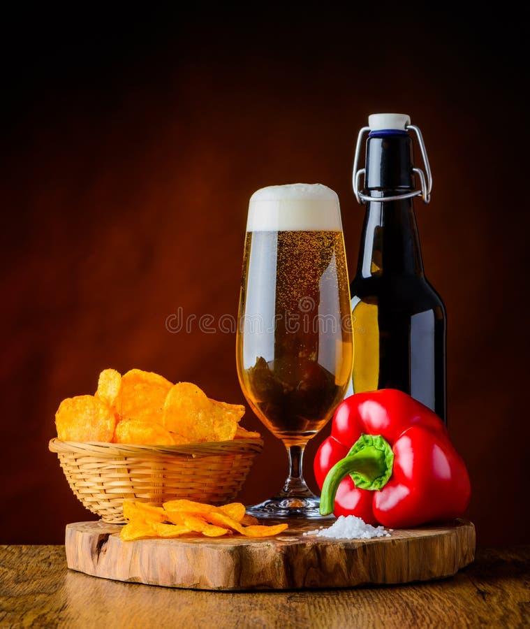 Bière et pommes chips avec le poivre photo libre de droits