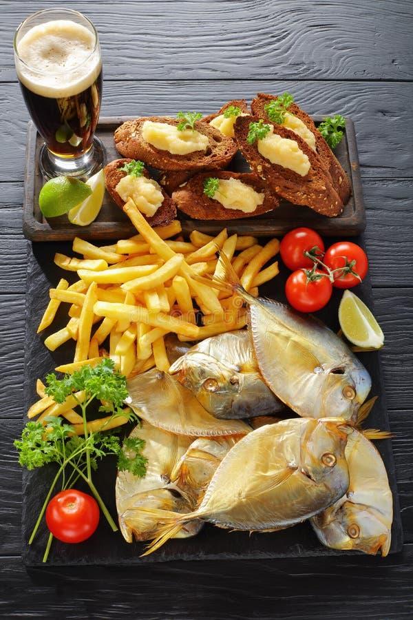 Bière, poissons fumés froids et pommes frites photo libre de droits
