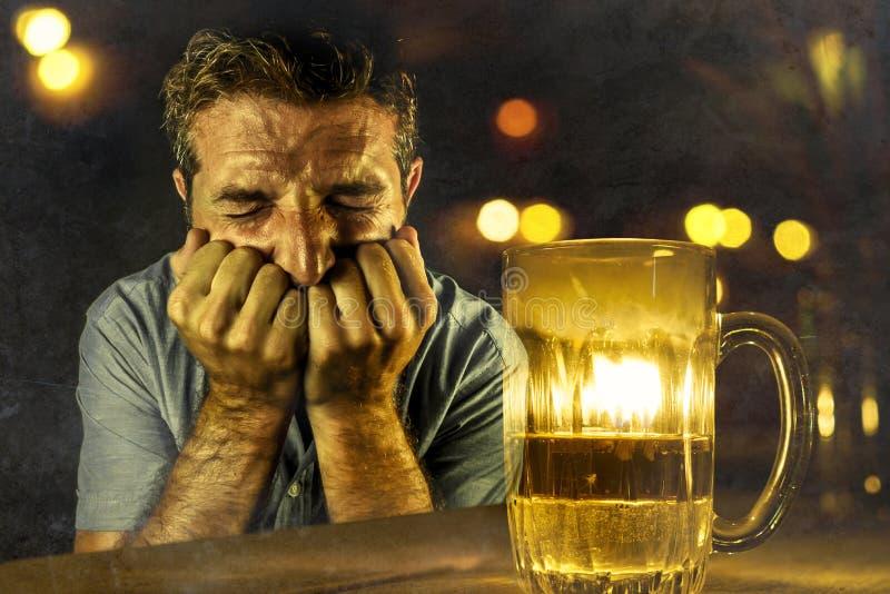 Bière potable d'homme alcoolique déprimé gaspillée et résistance échouante ivre à boire dans le bar de barre la nuit tombant dans image stock
