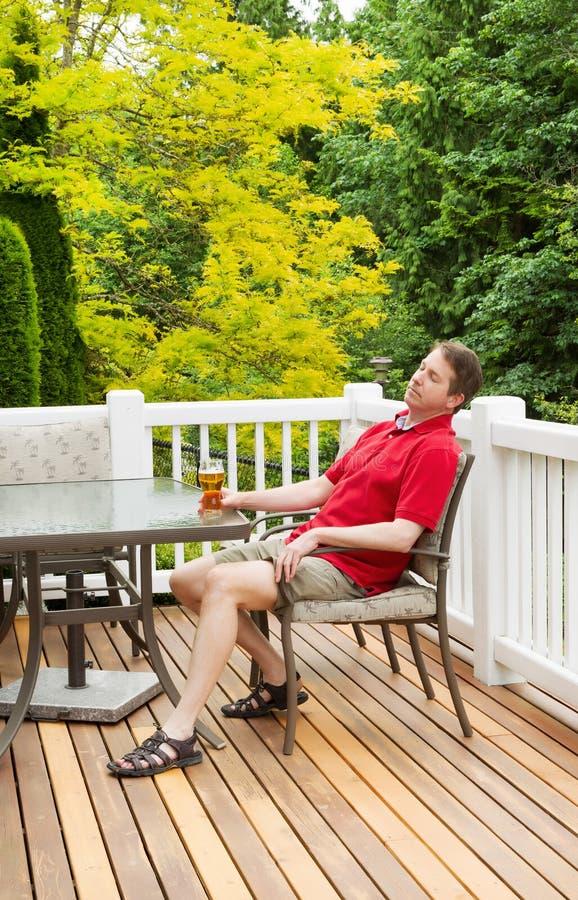 Bière potable d'homme paresseux tandis que dehors sur le patio photo stock