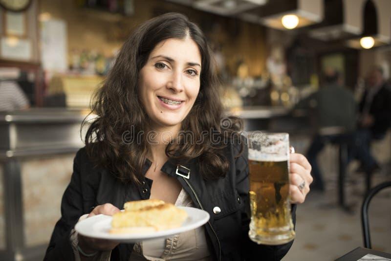 Bière potable de femme dans la barre photo libre de droits