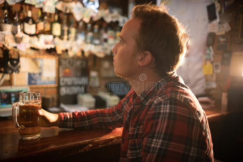 Bière potable de jeune homme réfléchi à la barre dans le bar irlandais reflecting photographie stock