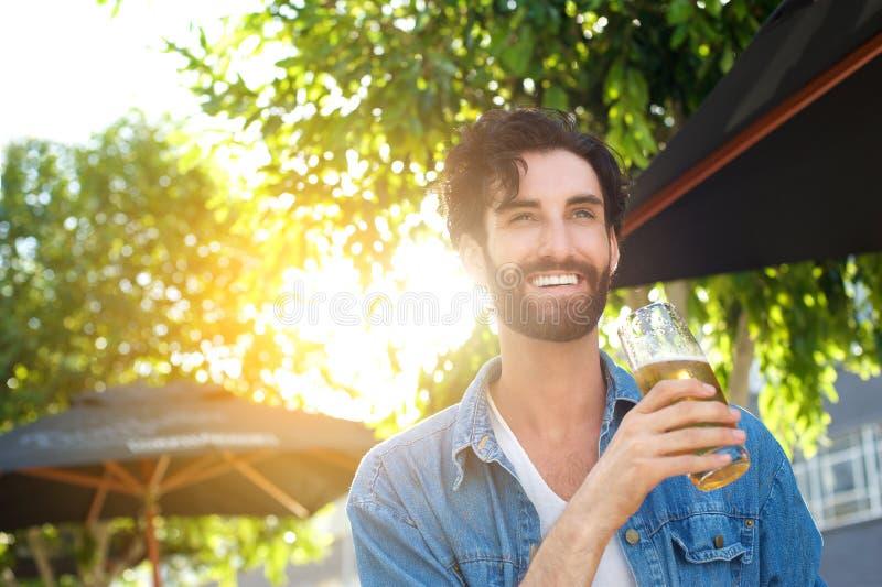 Bière potable de sourire de jeune homme à la barre extérieure en été image stock