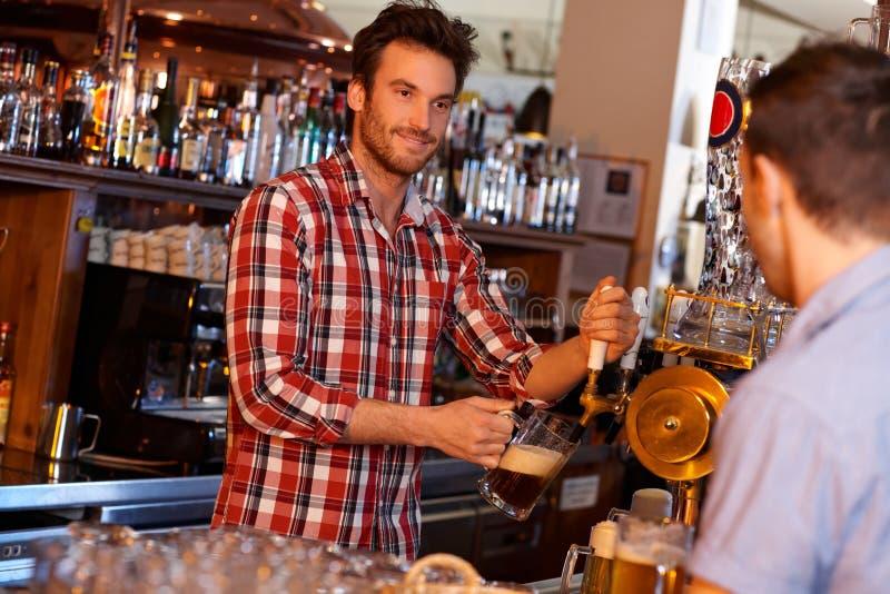 Bière pression de portion de barman dans le bar images stock