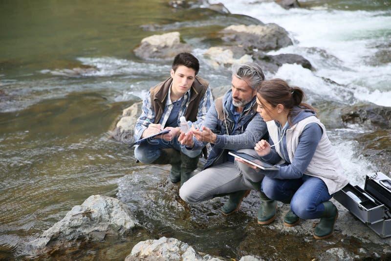 Biólogo com os estudantes que testam a água do rio imagem de stock royalty free