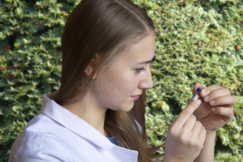 Biólogo de la mujer joven en líquido de colada de la capa blanca del tubo de ensayo en el pote con el suelo Brotes en fondo en in foto de archivo