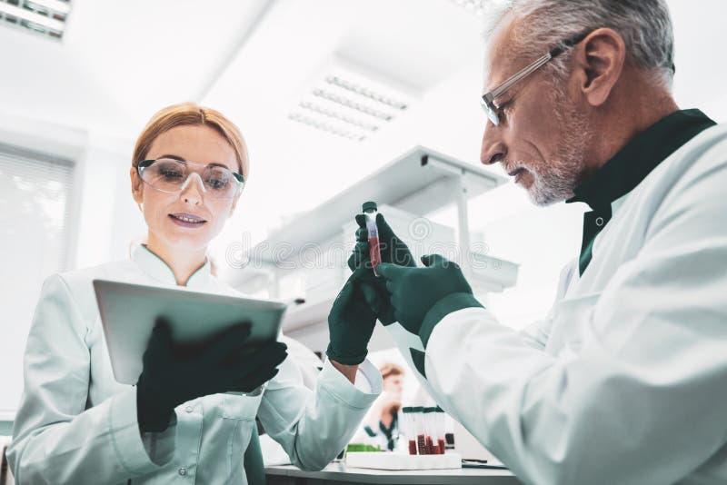 Biólogo novo que usa tecnologias modernas durante o trabalho imagens de stock royalty free