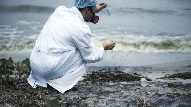 Biólogo que recoge la muestra de derrame de petróleo en el agua grande, prueba tóxica, ecosistema dañado foto de archivo