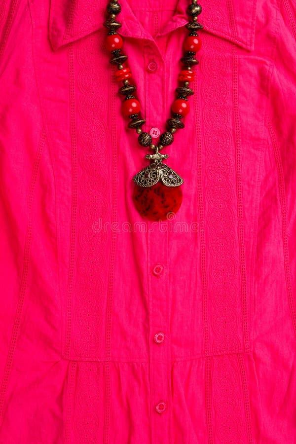 Biżuteria na różowej koszula obraz stock