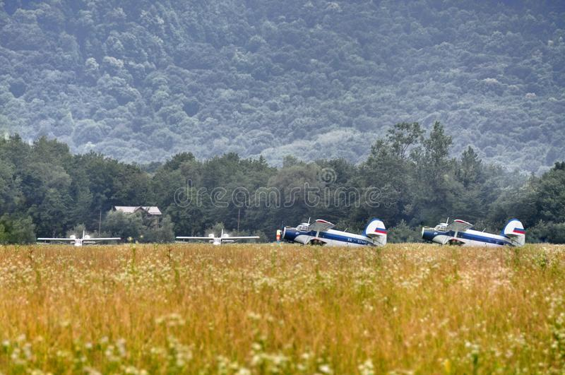 Bi-plane at the airfield. The plane in a field at the airport at the foot of the Caucasus mountains royalty free stock photo