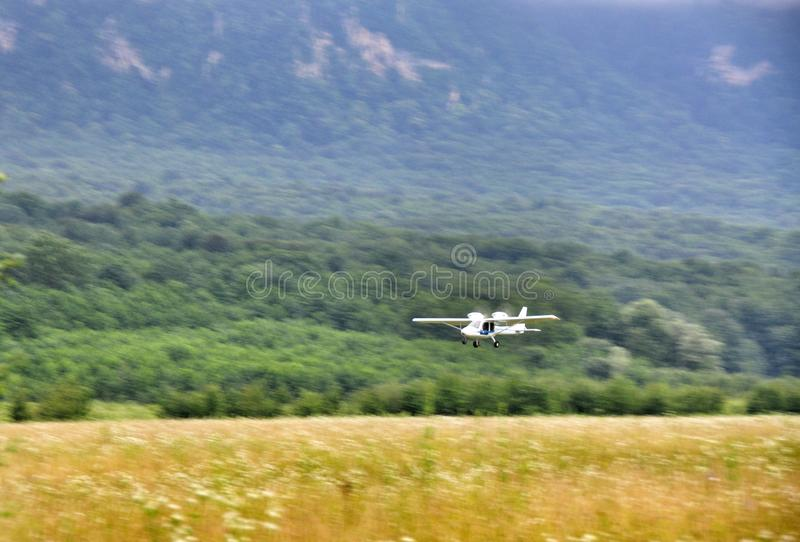 Bi-plane at the airfield. The plane in a field at the airport at the foot of the Caucasus mountains stock photography