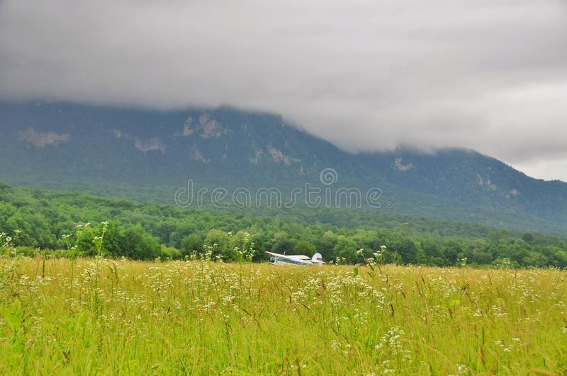 Bi-plane at the airfield. The plane in a field at the airport at the foot of the Caucasus mountains stock photos