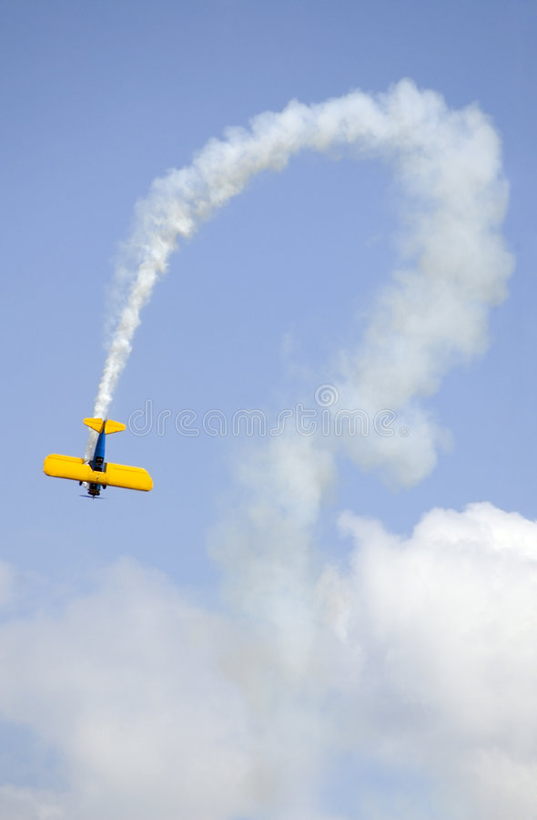 Bi-plane and Curved Smoke Trail stock photos
