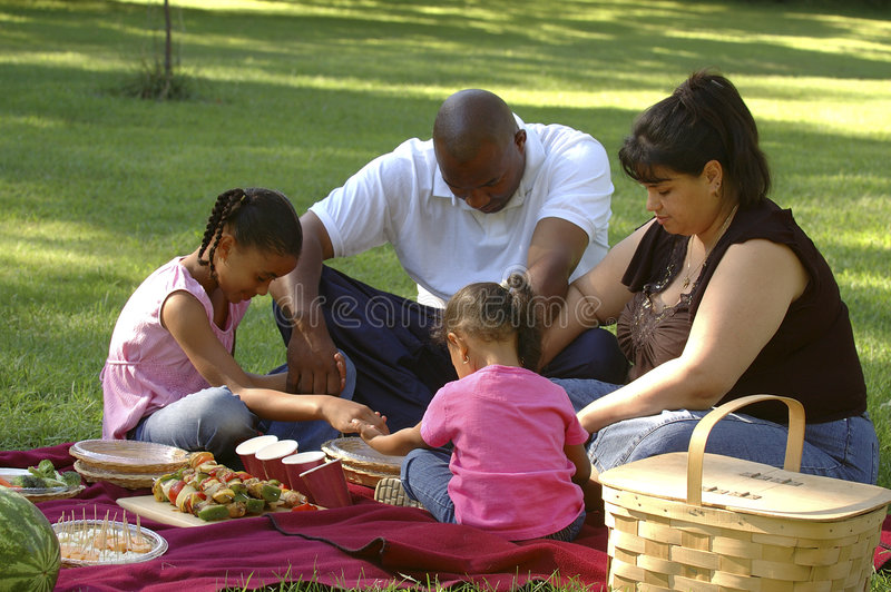 Bi-racial Family Picnic. African American dad, Hispanic mom and children on family picnic, saying grace before the meal stock photo