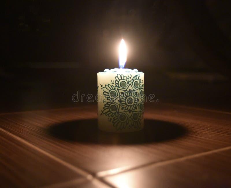 Biała świeczka z zielonym łania wzorem na nim fotografia stock