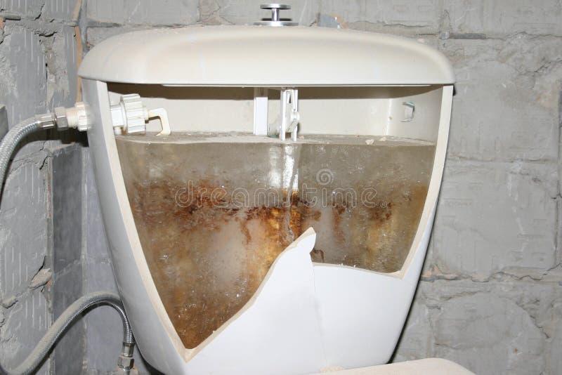 Biała ceramiczna toaletowego pucharu wodna szafa, wezbrana toaleta, klozetowy pełny lód w starej domowej chałupie bez ogrzewać w  obrazy stock