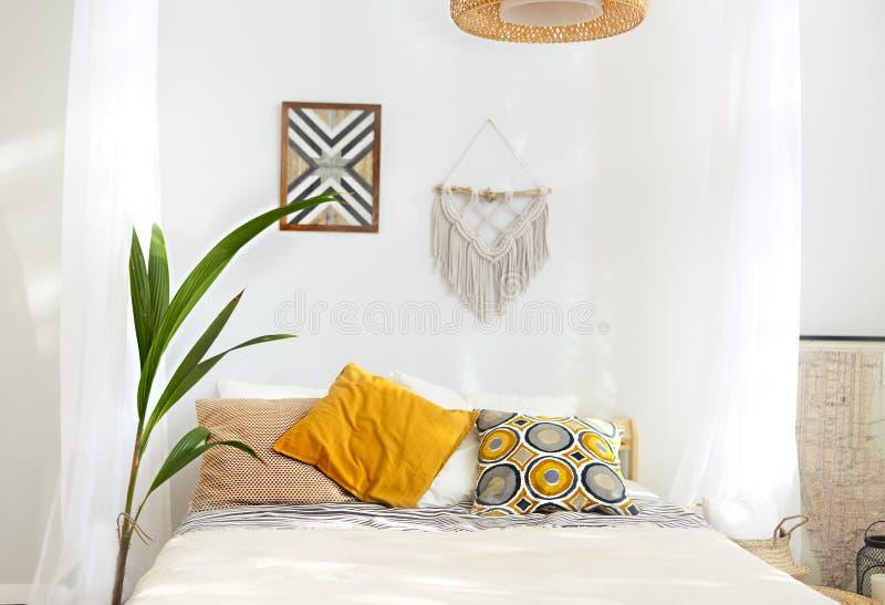 Biała i beżowa sypialnia w boho stylu z makramą zdjęcia stock