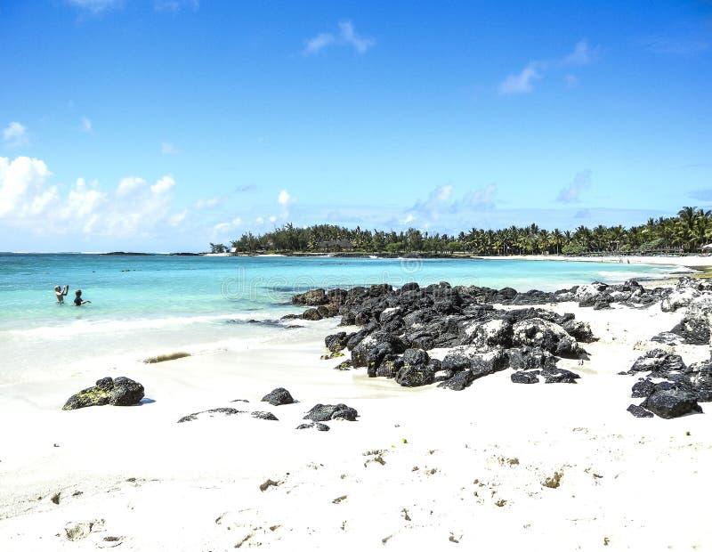 Biała piaskowata plaża wygina się wokoło małej zatoki z czernią kołysa w przedpolu obrazy royalty free