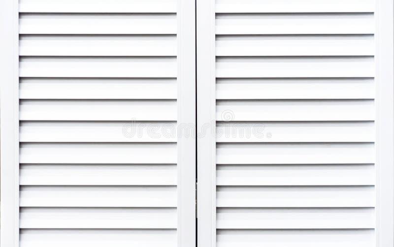 Białe drewniane żaluzje ochraniać okno od światła słonecznego obraz royalty free