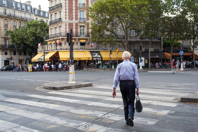 Białogłowy mężczyzna krzyżuje ulicę na zebry zwyczajnym droga przemian w Południowym Paryż fotografia royalty free