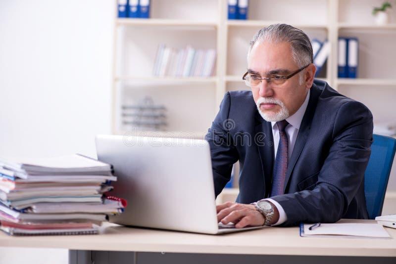Biały brodaty stary biznesmena pracownik nieszczęśliwy z przesadną pracą obraz royalty free