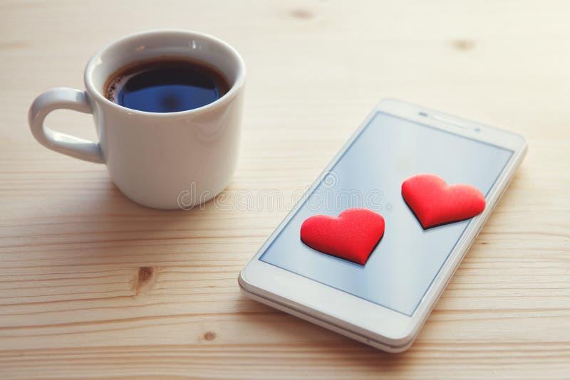 Biały kawy espresso smartphone z dwa czerwonymi sercami i filiżanka zdjęcia stock