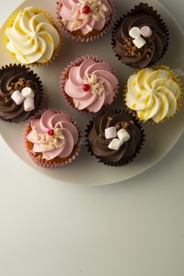 biały kolorowe tło babeczki Menchie, kolor żółty i czekolad babeczki, karmowy cząber Słodki deseru lub śniadania przyjęcie, zdjęcie royalty free