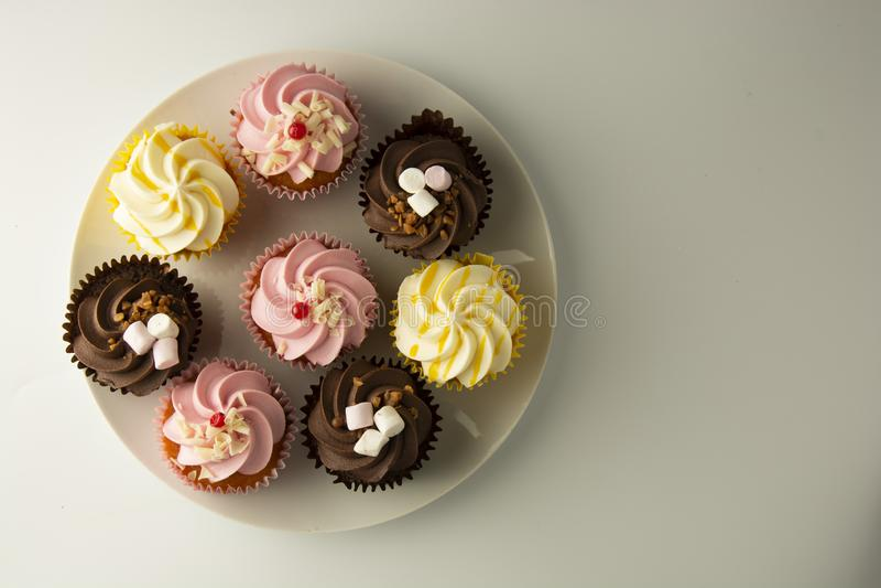 biały kolorowe tło babeczki Menchie, kolor żółty i czekolad babeczki, karmowy cząber Słodki deseru lub śniadania przyjęcie, obraz stock